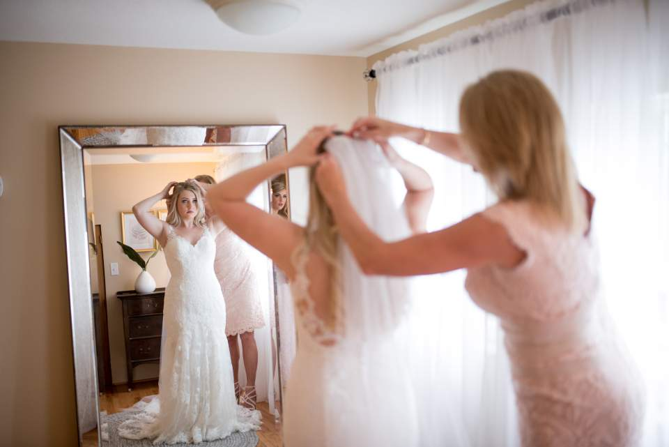 mom helping daughter with her veil