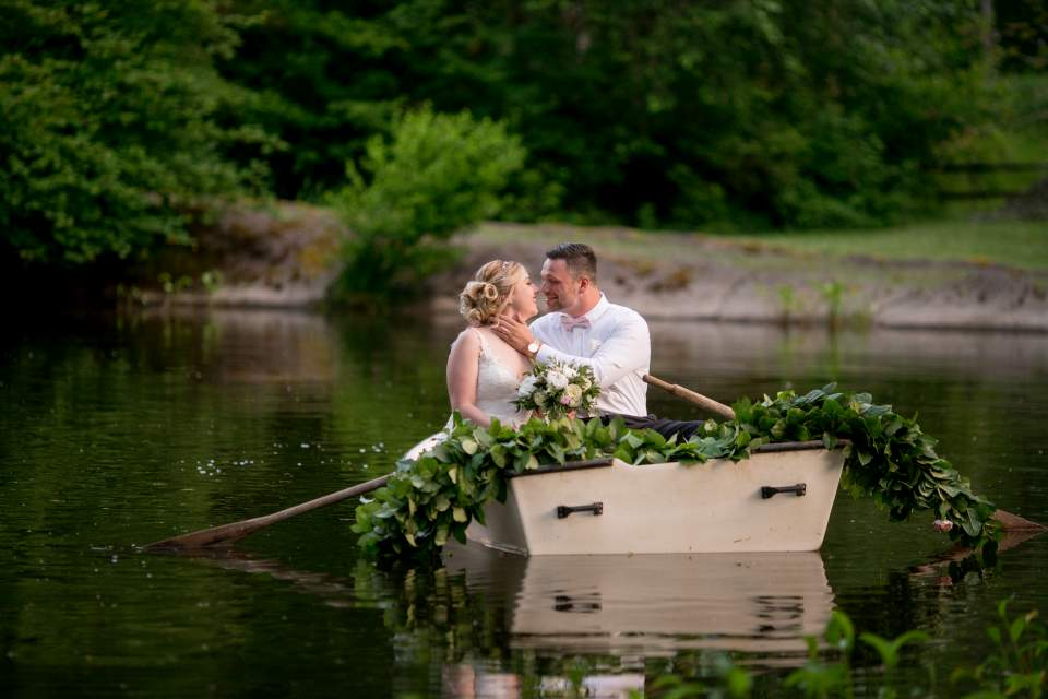 romantic wedding photos with bride and groom in a rowboat