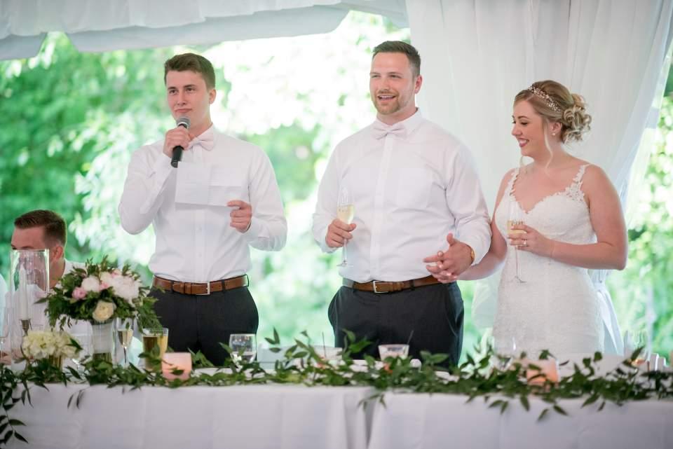 toasts inside tented wedding reception