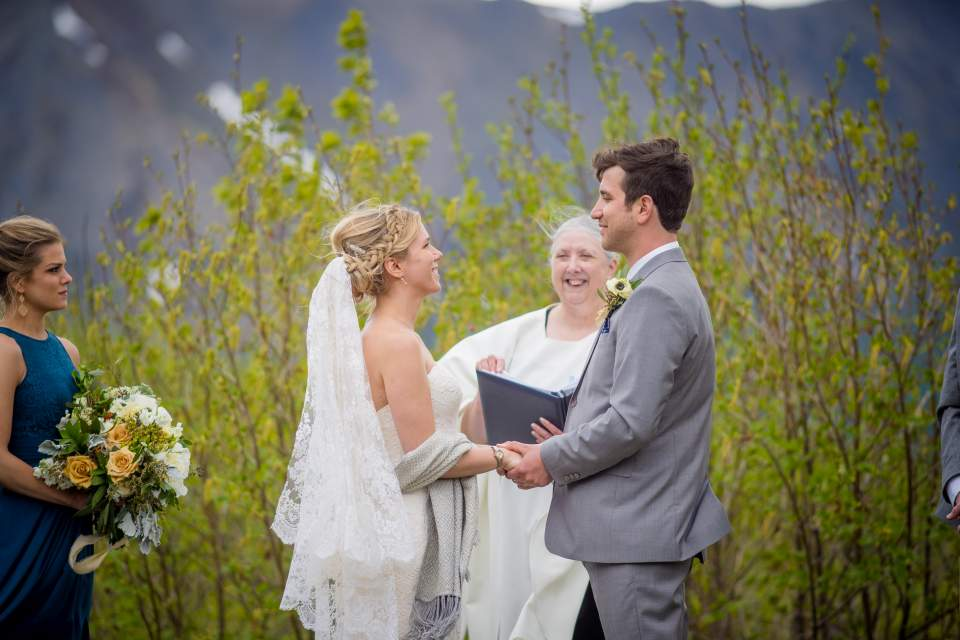 bride and groom exchanging rings in front of mountains