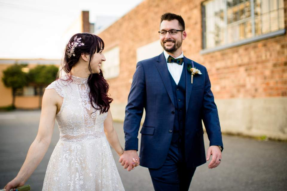 bride and groom happily walking down alley