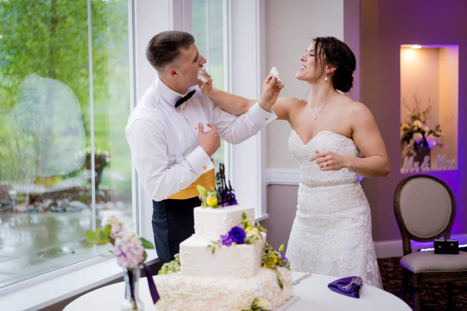 bride and groom having cake fight