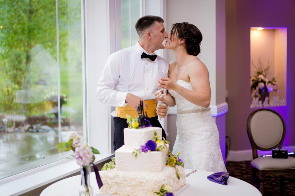 bride and groom kiss after getting cake on each other