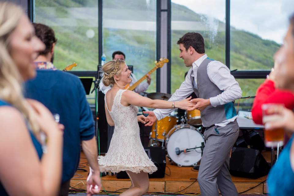 bride and groom swing dancing in front of live band