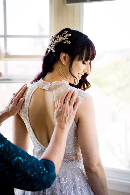 bride getting dressed for wedding