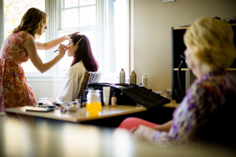 bride getting make up on in house before wedding