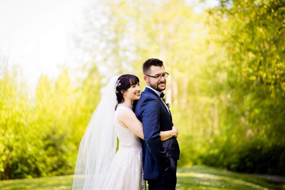bride hugging groom for photo on wedding day