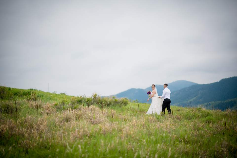 bride leading groom down trail in colorado mountains