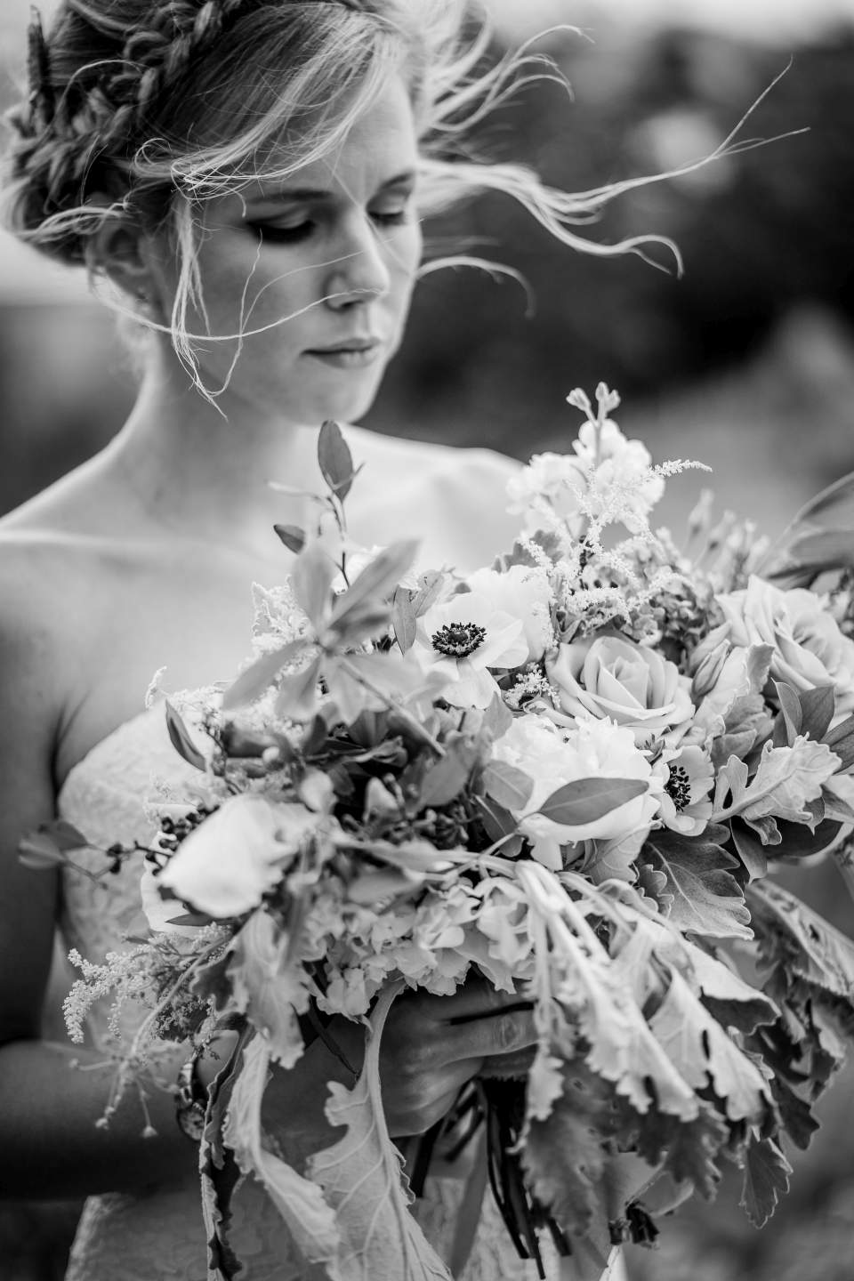 bride looking at flowers while her hair blows in the wind
