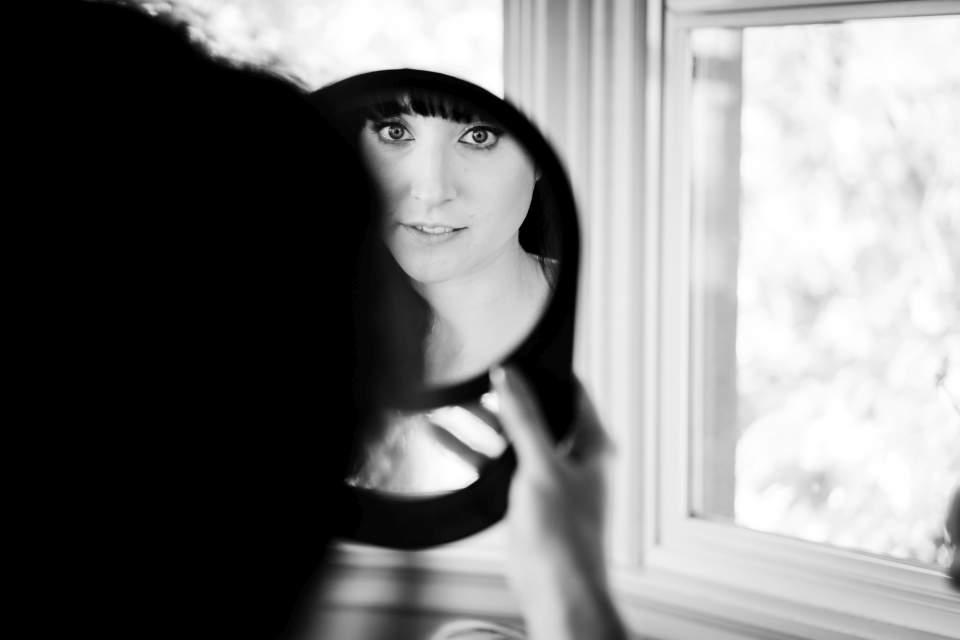 bride looking in mirror at make up