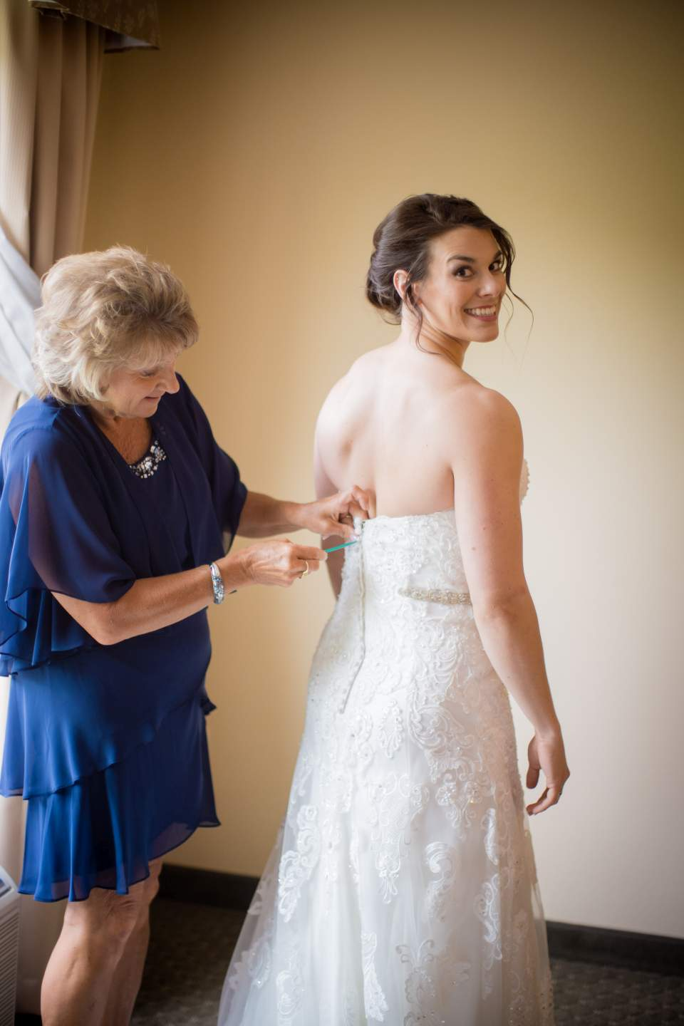 bride smiling while she gets ready for her wedding