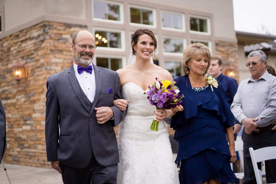 bride walking down aisle with her parents