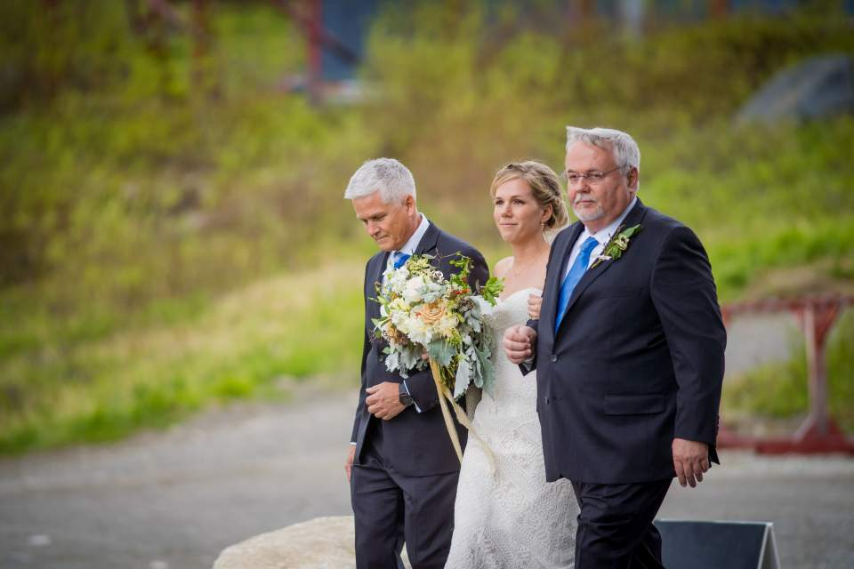 bride walks down aisle with her dads
