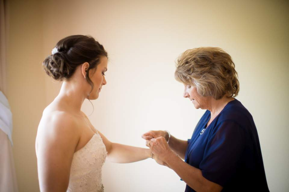 brides mom helping with jewelry