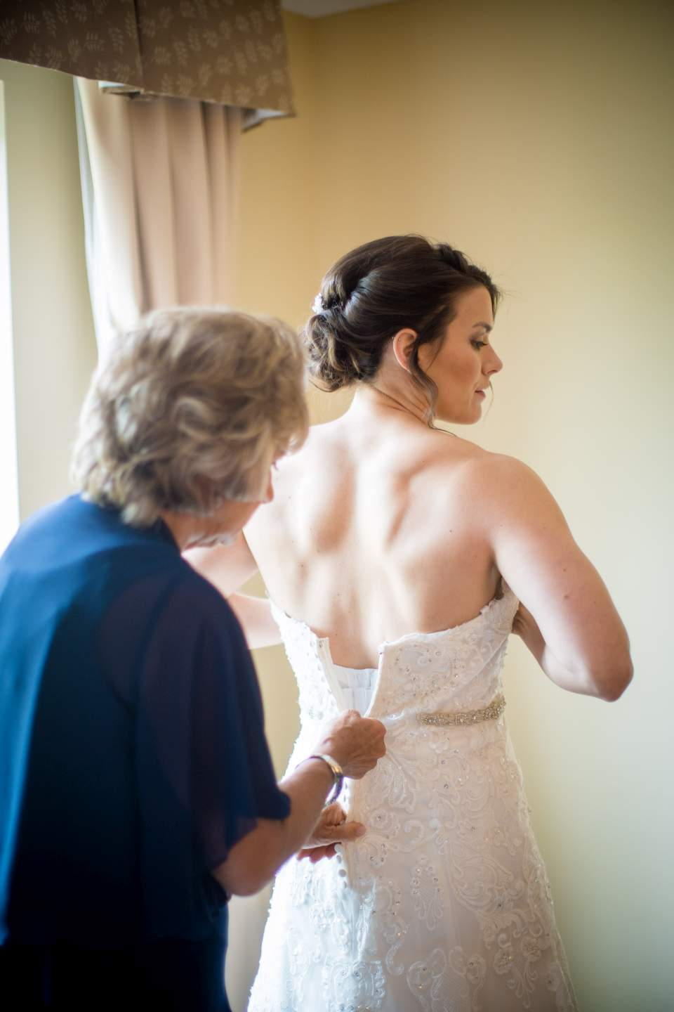 brides mom zipping up wedding dress