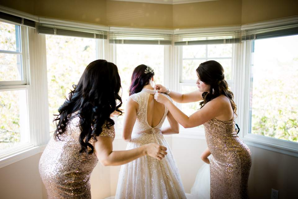bridesmaids helping bride get into dress