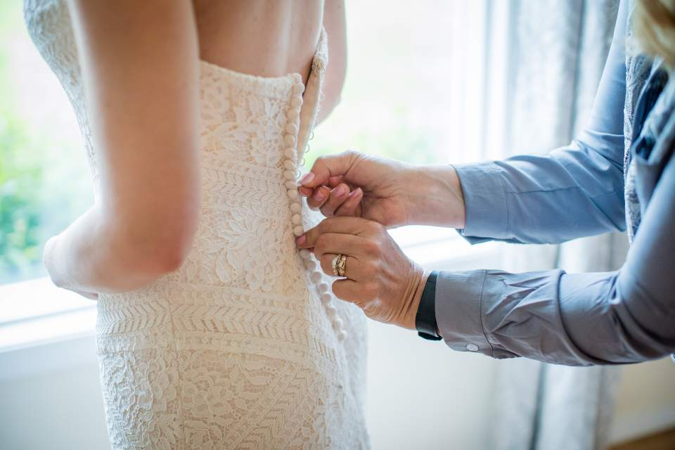 close up of bride being zipped into dress