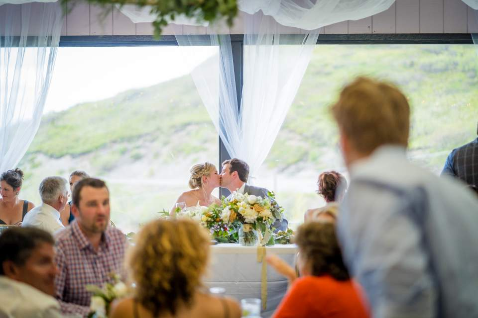 couple shares kiss at head table