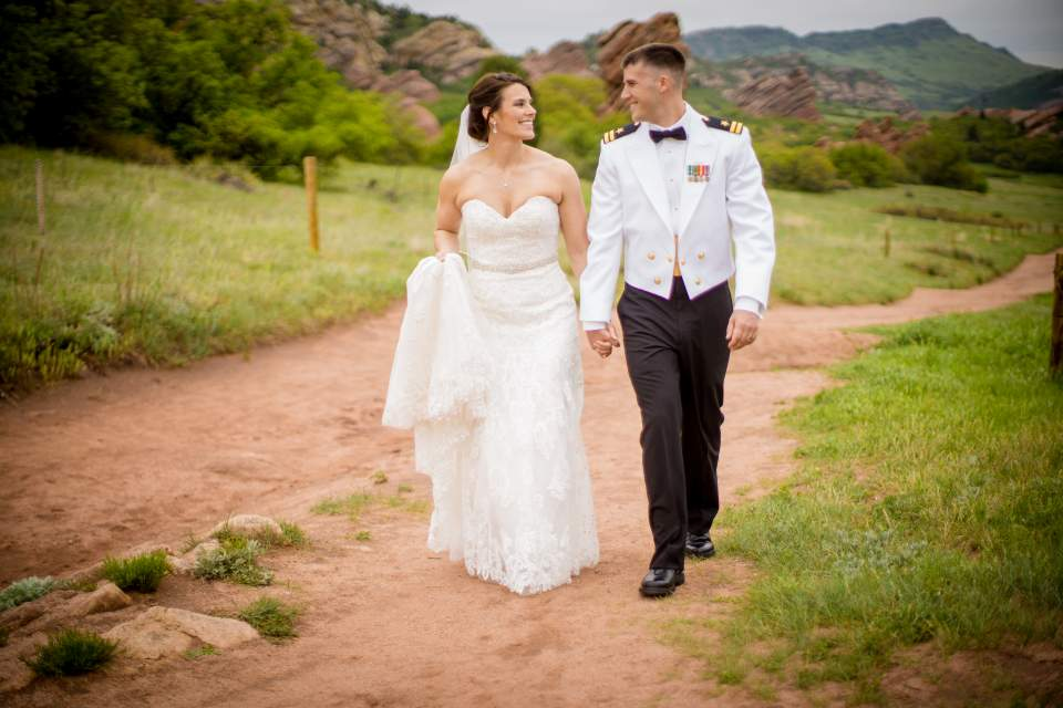 couple walking in park with colorado red rocks