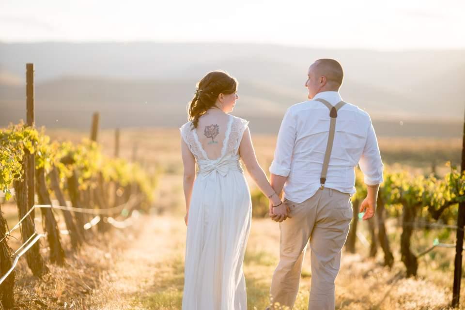 couple walking through winery at sunset