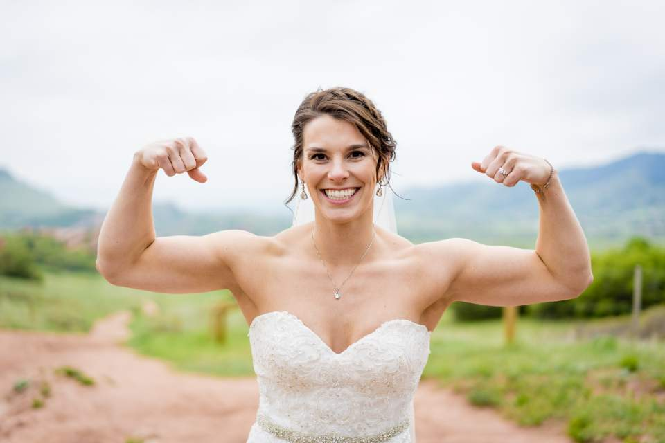 crossfit strong bride flexing her muscles in her wedding dress