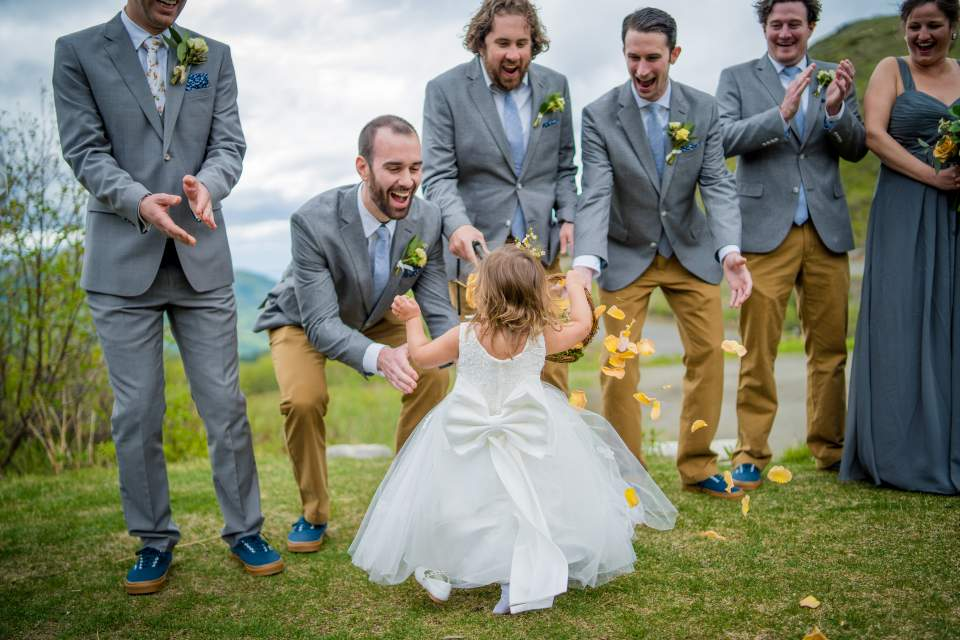 flower girl running to her dad and spilling flower petals