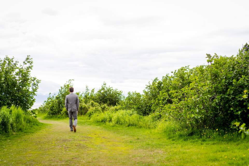groom walking to first look spot