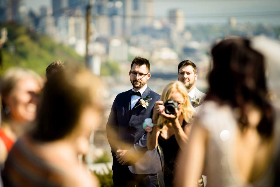 groom watching bride walk down aisle at ella bailey park