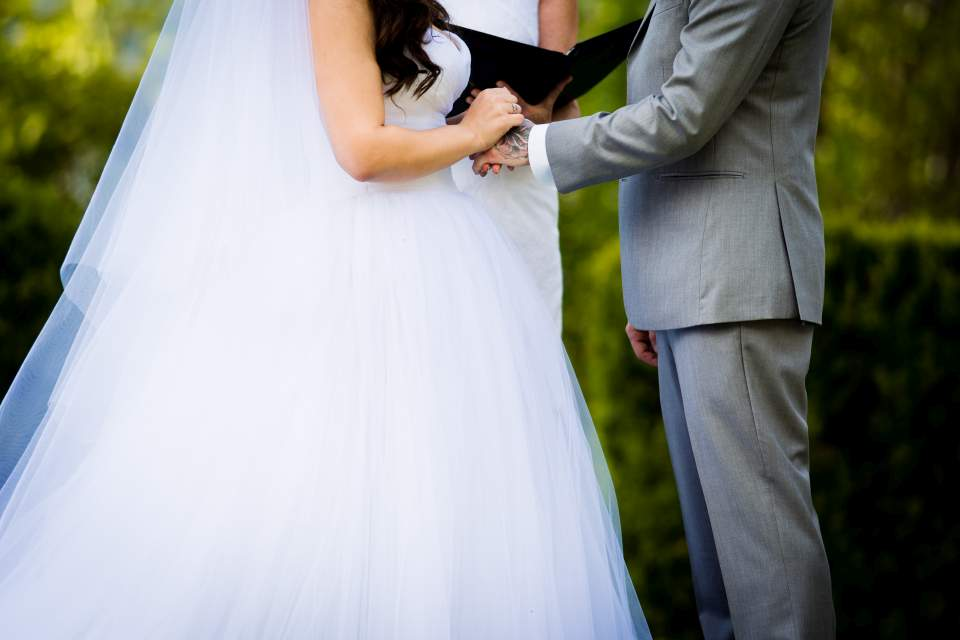 husband and wife embracing during wedding ceremony lake quinault lodge