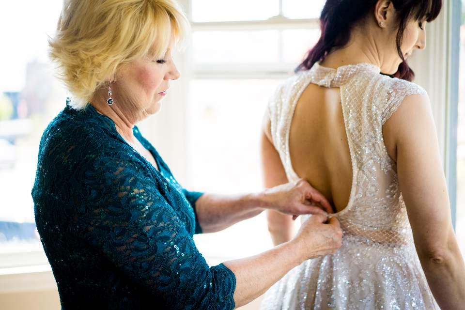 mom buttoning brides wedding dress