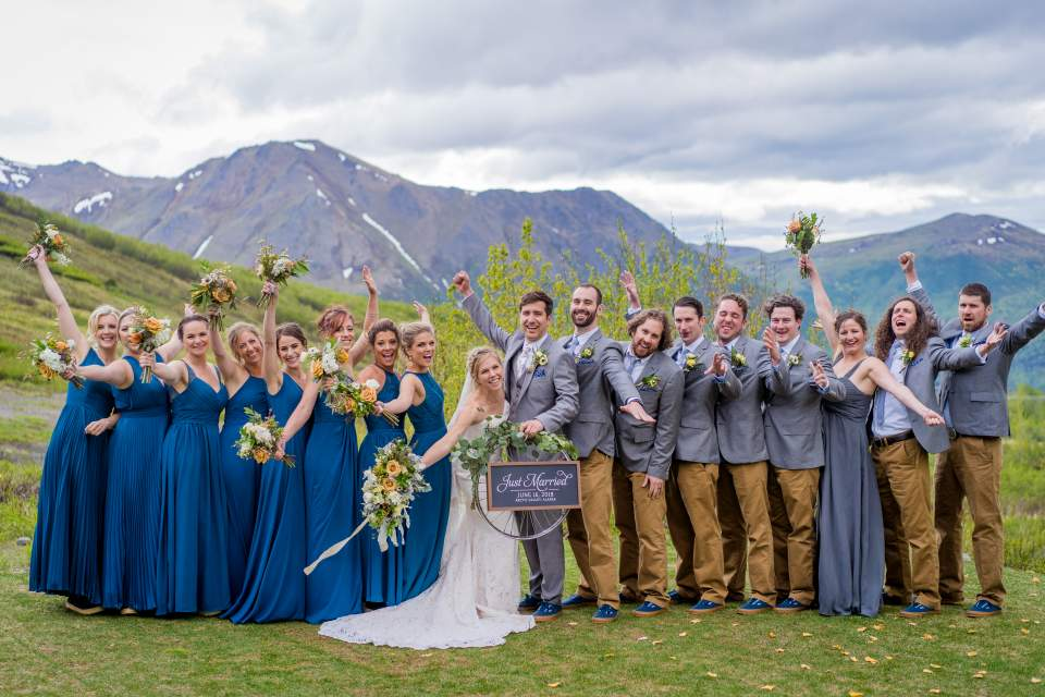 wedding party cheering on bride and groom mountain backdrop