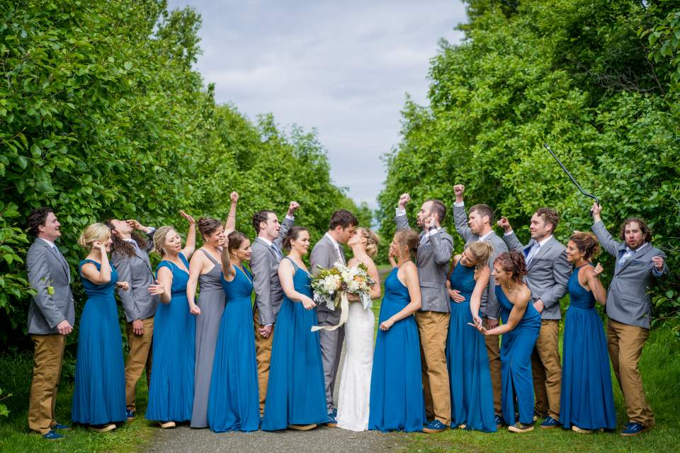 wedding party cheering on couple as they kiss