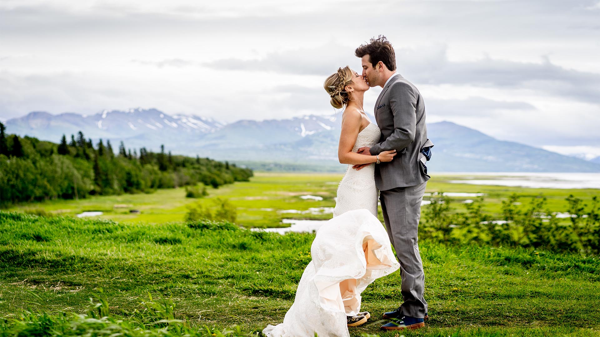 bride and groom kiss on windy spring anchorage wedding day