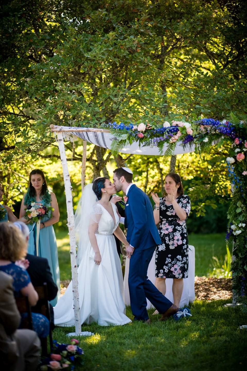 bride and groom kissing under chuppah