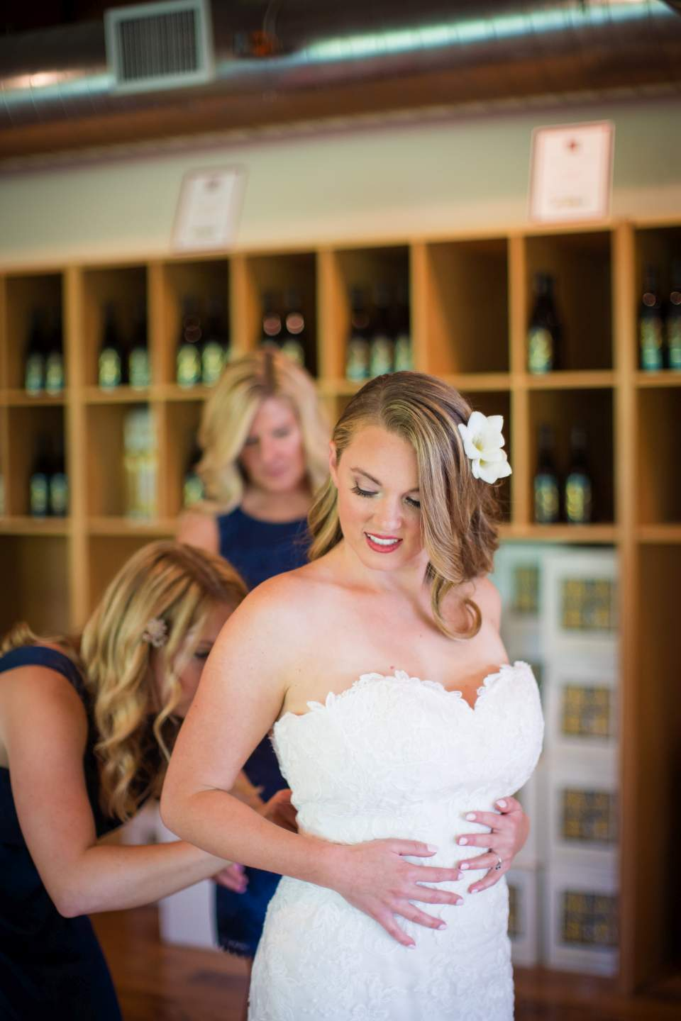 bride and mom putting dress on