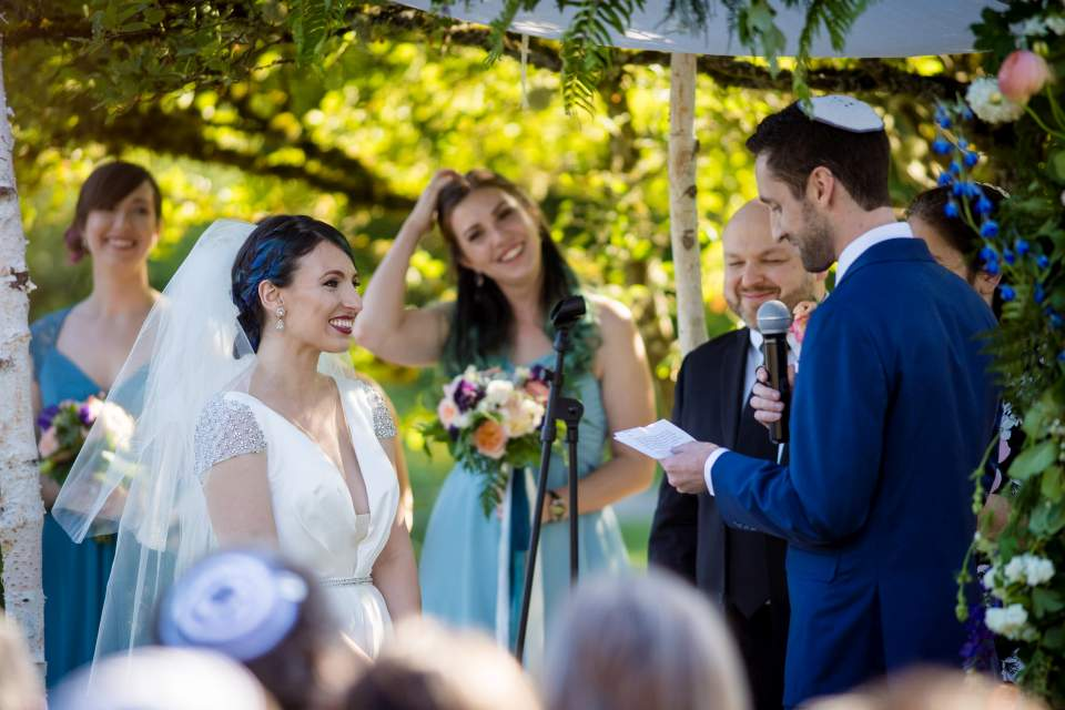 bride smiling at grooms wedding vows
