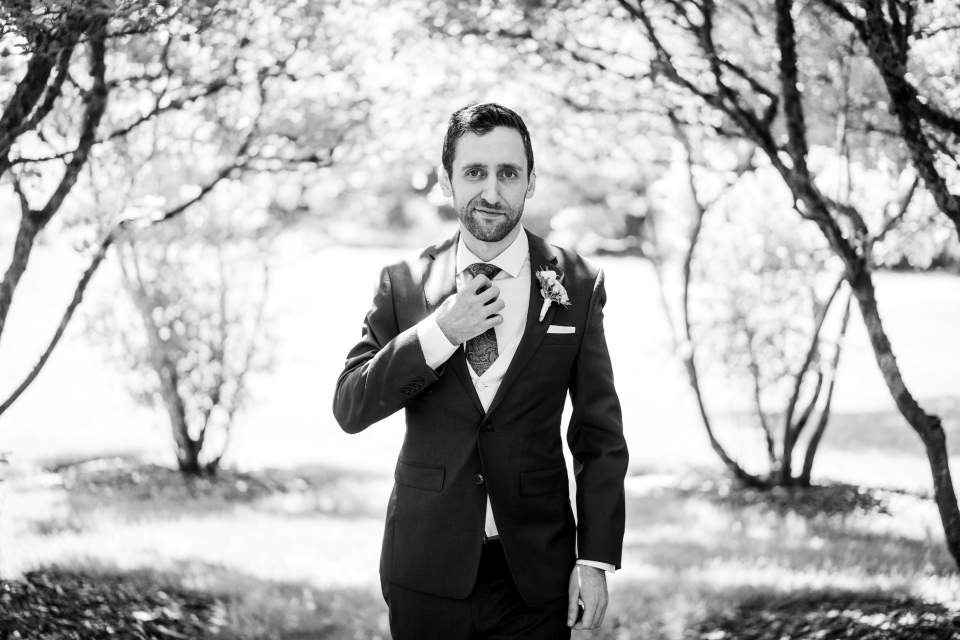 dapper groom walking towards camera