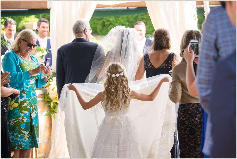 flower girl carrying wedding train documentary wedding photography