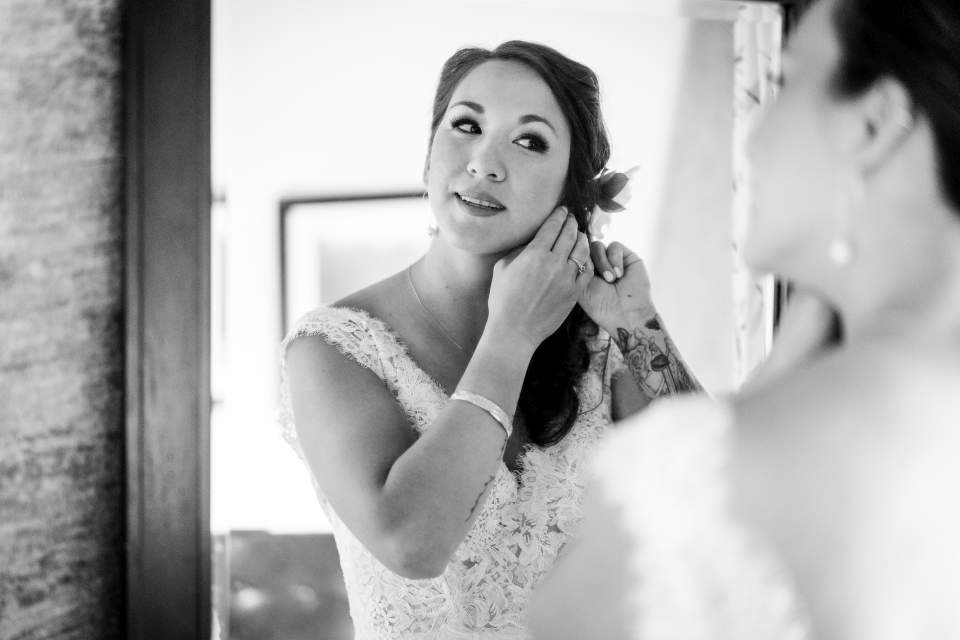 gorgeous bride putting earrings on in mirror