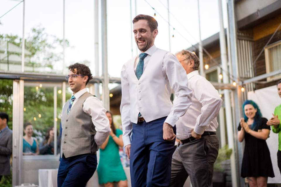 groom fun dance with brother and dad