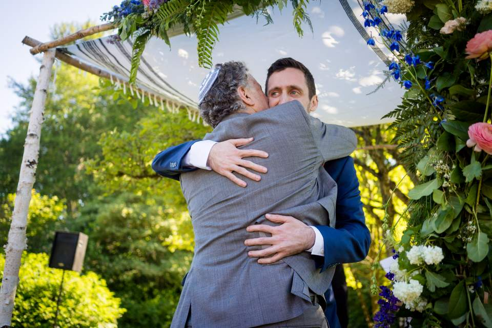 groom hugging father during wedding ceremony