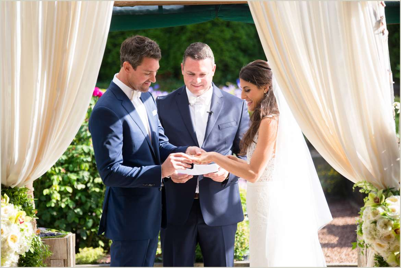 groom slipping wedding ring on brides finger