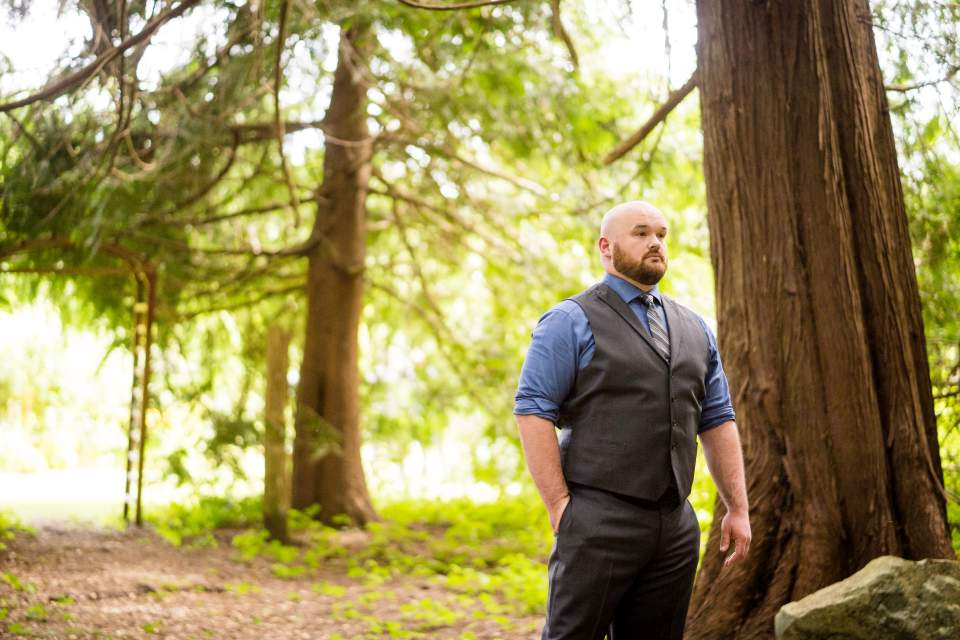 groom waiting for first look in the forest