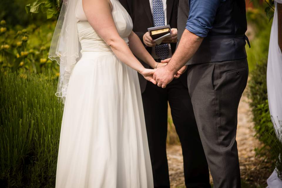 husband and wife holding hands wedding ceremony
