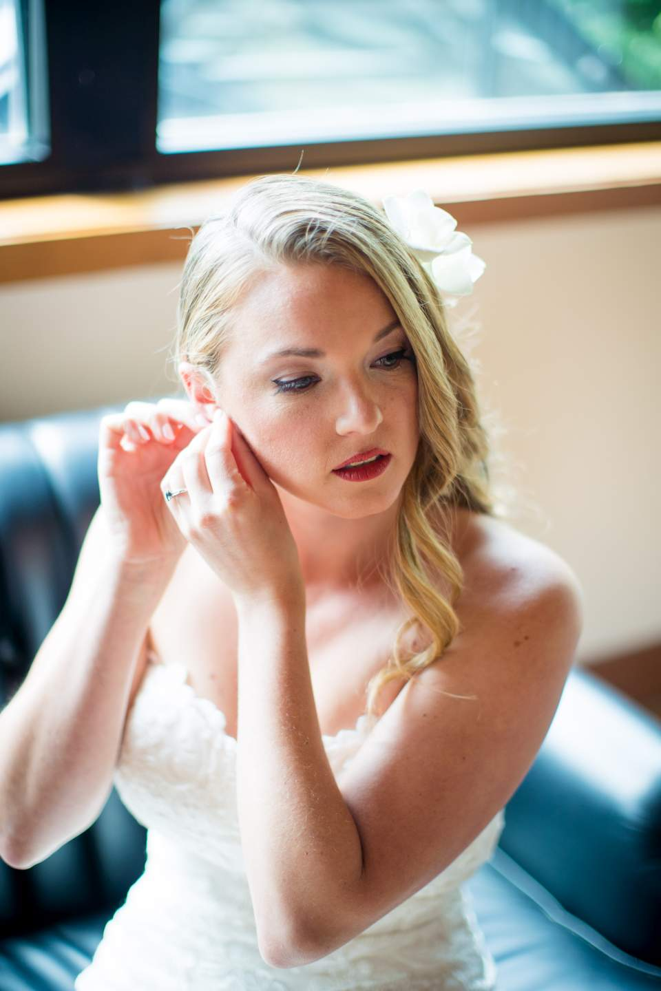 stunning bride putting earrings on