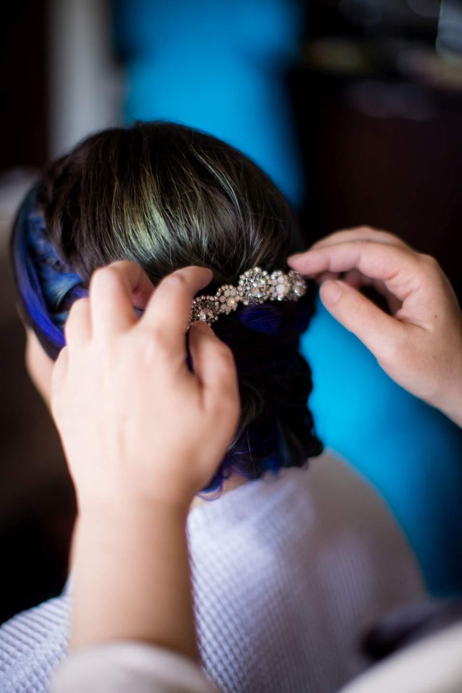stylist putting clip in brides hair