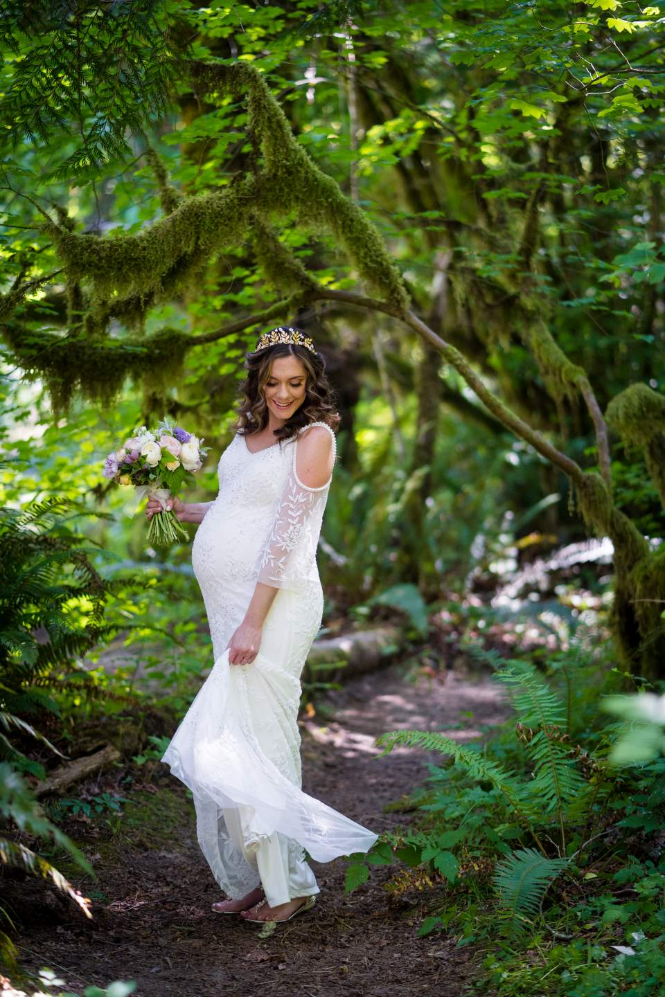 beautiful bride twirling in boho wedding dress in the mossy forest at treehouse point