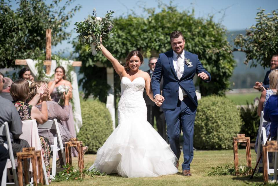 bride and groom cheer as they exit ceremony