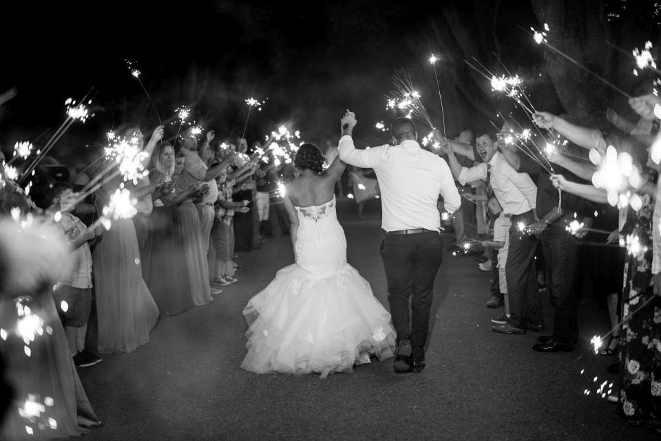 bride and groom cheer as they leave wedding reception to a sparkler exit