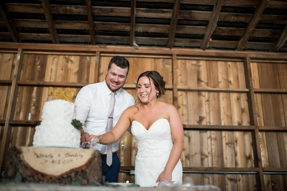 bride and groom cutting wedding cake barn wedding